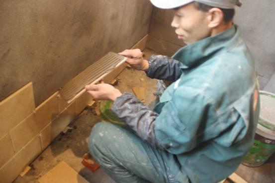 正在采用薄贴法贴砖的工人